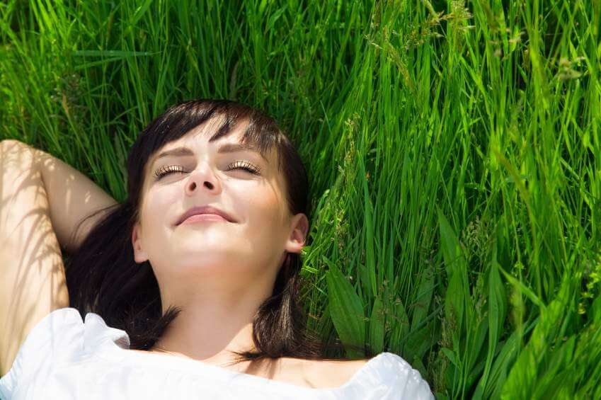 Lady relaxing in grass, relaxing and reconnecting.
